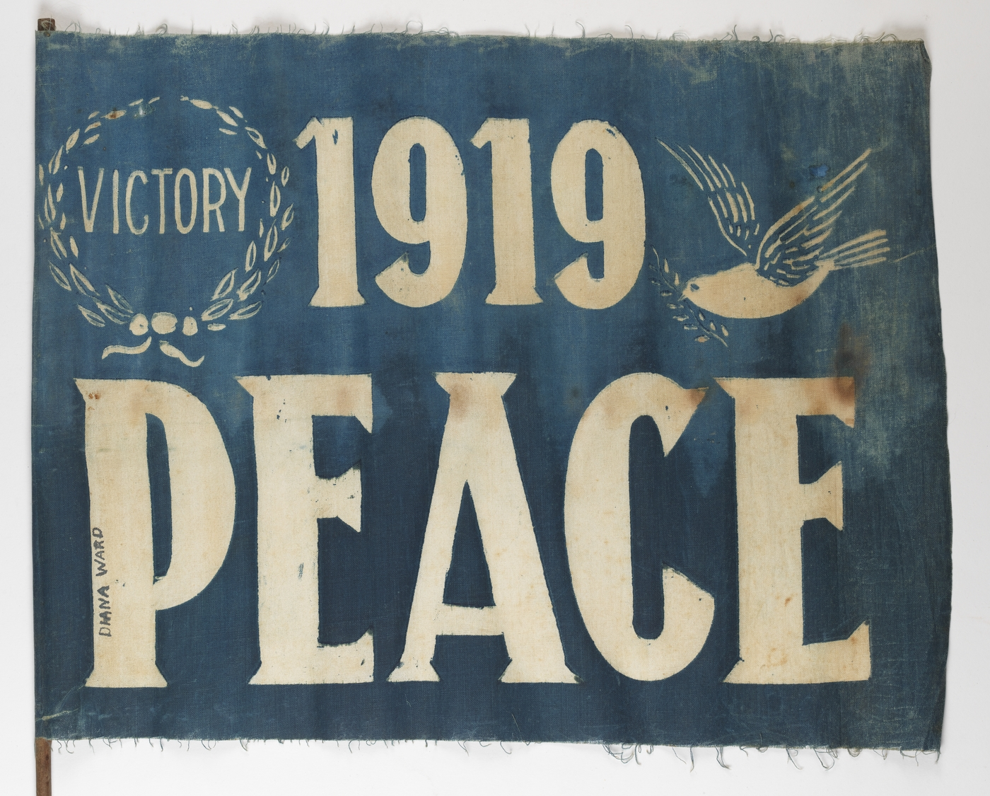 "A blue flag with stencilled white lettering that declares ""Victory, 1919 PEACE"""