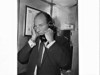 British racing car driver Stirling Moss uses a public phone on arrival at Mascot