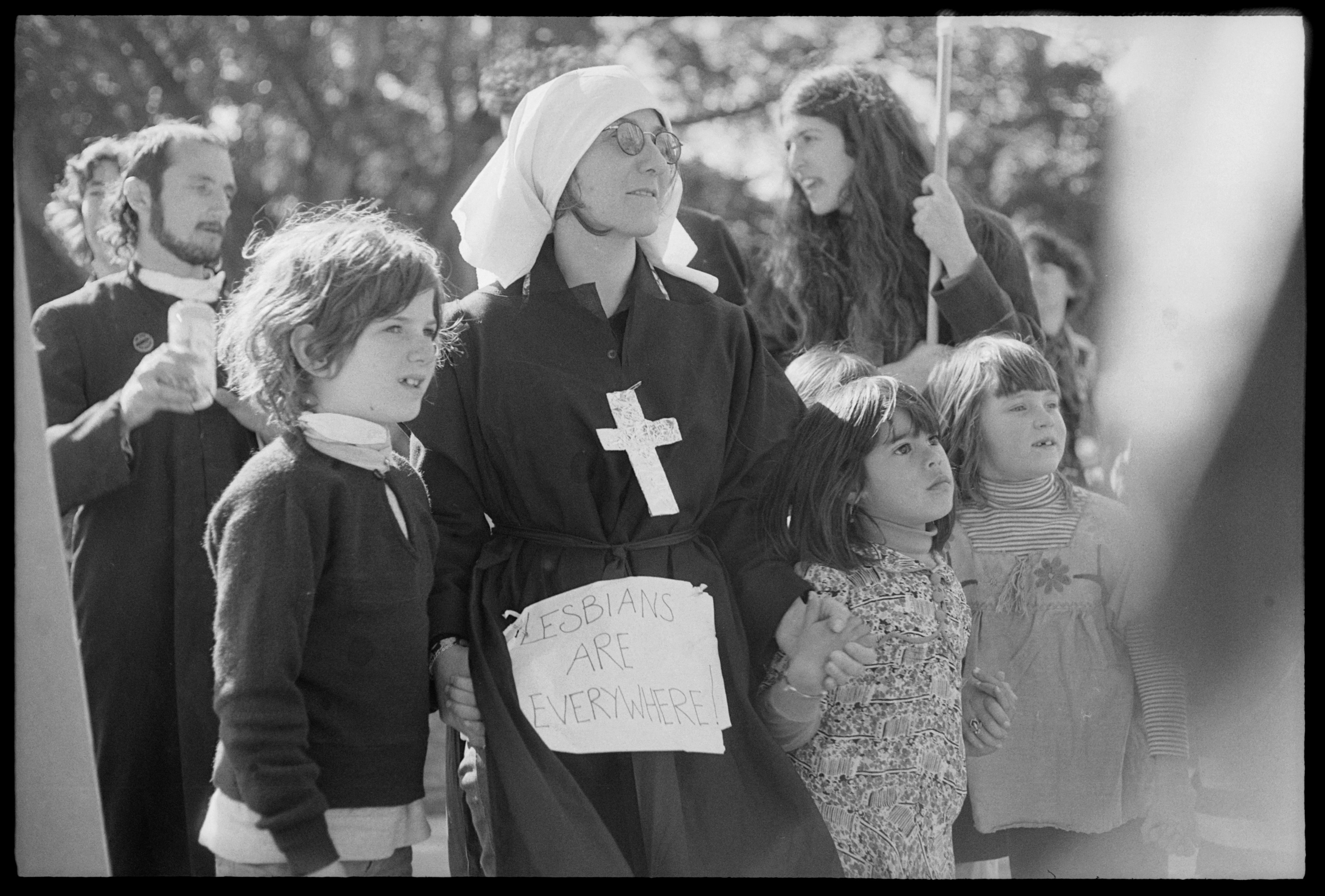 Placard: 'Lesbians are Everywhere', pinned to mock habit of woman with three children at gay liberation demonstration, Hyde Park, Sydney. Tribune Collection